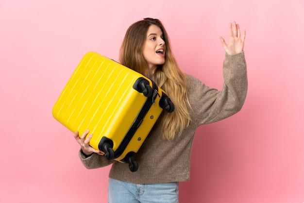 Junge blonde frau über isolierte wand im urlaub mit reisekoffer und gruß