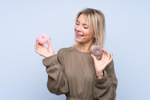 Junge blonde frau über isolierten blauen wandhalterungskrapfen mit glücklichem ausdruck