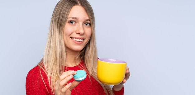 Junge blonde frau über isolierter blauer wand, die bunte französische macarons und eine tasse milch hält