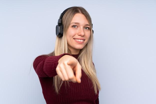 Junge blonde frau über isolierter blauer wand, die musik hört und nach vorne zeigt