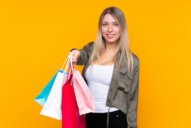 Junge blonde frau über isolierter gelber wand, die einkaufstaschen hält und sie jemandem gibt