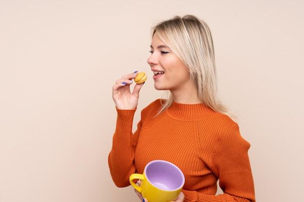 Junge blonde frau über isolierter wand, die bunte französische macarons und eine tasse milch hält