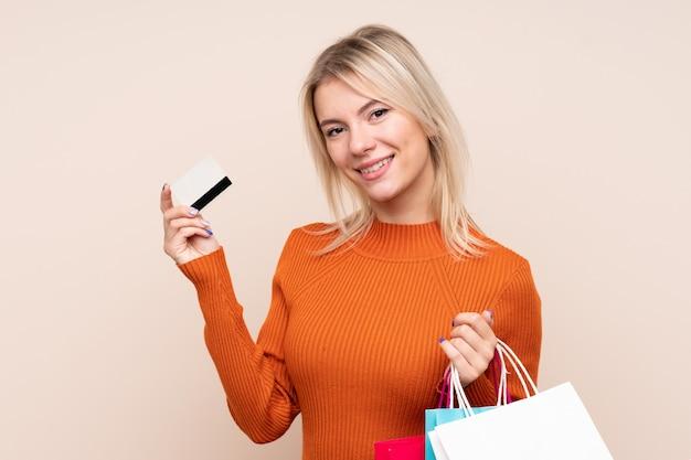 Junge blonde frau über isolierter wand, die einkaufstaschen und eine kreditkarte hält