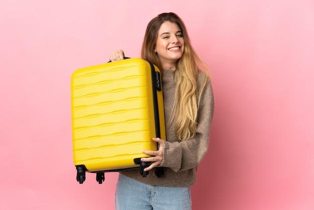 Junge blonde frau über isolierter wand im urlaub mit reisekoffer