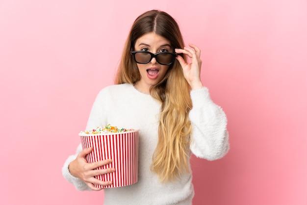 Junge blonde frau über isolierter wand überrascht mit 3d-brille und hält einen großen eimer popcorn
