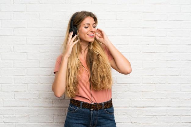 Junge blonde frau über weißer backsteinmauer hörend musik mit kopfhörern