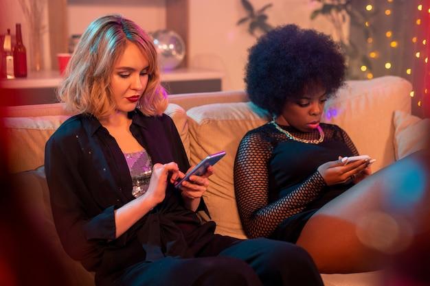 Junge blonde frau und ihre freundin afrikanischer ethnizität, die in sozialen netzwerken scrollen oder sms schreiben, während sie sich auf der couch zu hause entspannen