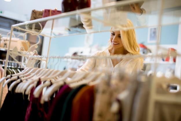 Junge blonde frau wählt eine kleidung im laden