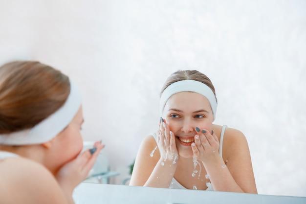 Junge blonde frau wäscht reines wasser des gesichts im waschbecken im badezimmer. jugendlich mädchen reinigen gesichtshaut. self care morgenroutine frau porträtreflexion im spiegel. tägliche gesichtshygiene.