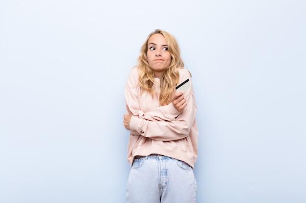 Junge blonde frau zuckt die achseln, fühlt sich verwirrt und unsicher, zweifelt mit verschränkten armen und verwirrtem blick und hält eine kreditkarte