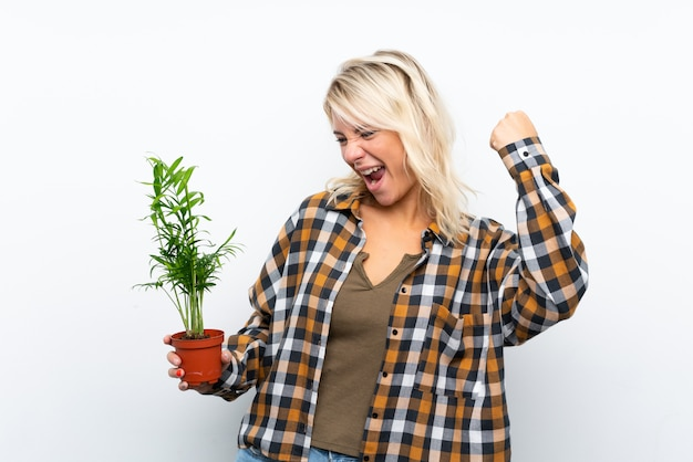 Junge blonde gärtnerfrau, die eine anlage über dem lokalisierten weiß feiert einen sieg hält