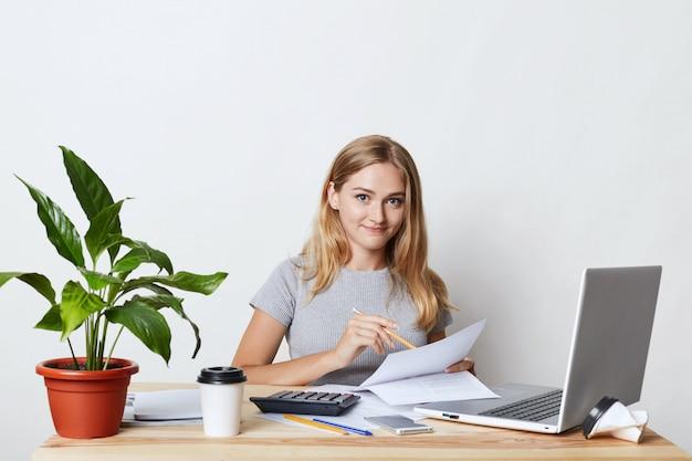 Junge blonde geschäftsfrau, die an ihrem arbeitsplatz sitzt, während geschäftsbericht erstellt, jahreszahlen berechnet, dokumente liest und moderne technologien für ihre arbeit verwendet, kaffee zum mitnehmen trinkt