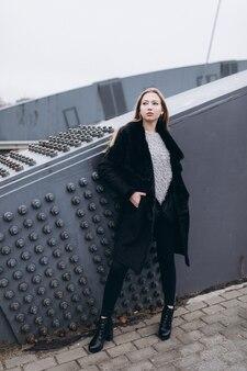 Junge blonde geschäftsfrau nahe brücke. wandern entlang der europäischen stadt