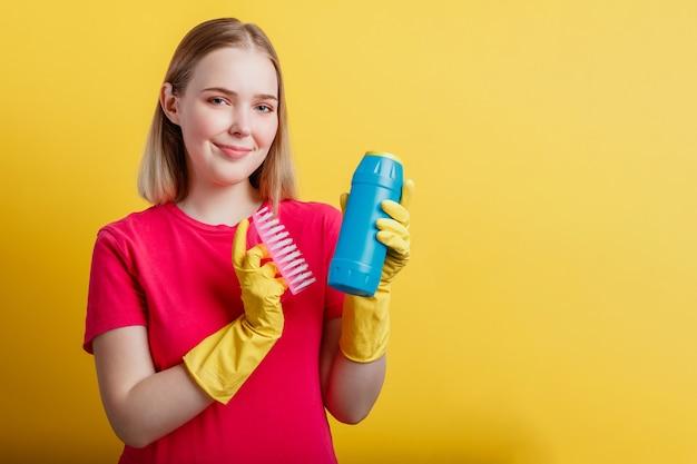 Junge blonde glückliche lächelnde frau, die bereit ist, haus mit haushaltswaren einzeln auf gelbem farbhintergrund zu säubern. frauenportrait mit reinigungsbürstenreiniger in gummihandschuhen. platz kopieren.