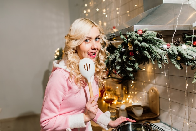 Junge blonde hausfrau, die weihnachtsessen in der küche vorbereitet