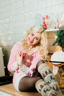 Junge blonde hausfrau, die weihnachtsessen in der küche zubereitet