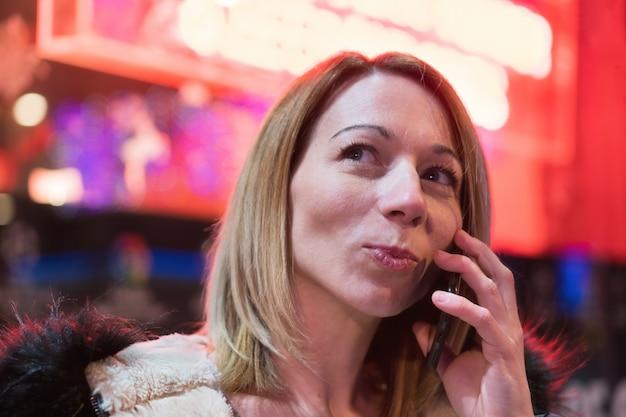 Junge blonde hübsche frau, die am telefon im stadtzentrum nachts spricht. rote neonlichter im hintergrund.