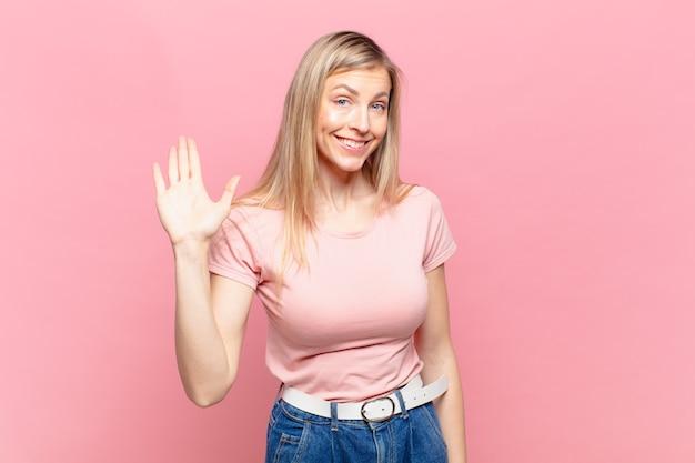 Junge blonde hübsche frau, die glücklich und fröhlich lächelt, die hand winkt, sie begrüßt und begrüßt oder sich verabschiedet