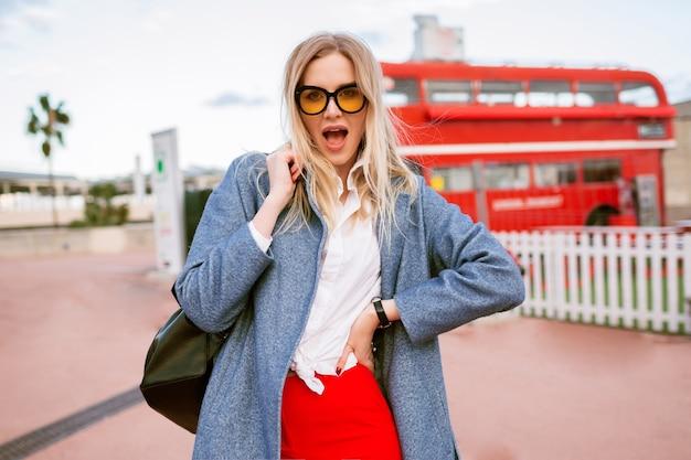 Junge blonde hübsche frau, die im stadtzentrum von london geht und stilvolles, schickes, lässiges studentenoutfit, blauen mantel und farbige brille trägt, herbstfrühling, zwischensaison, reisestimmung.
