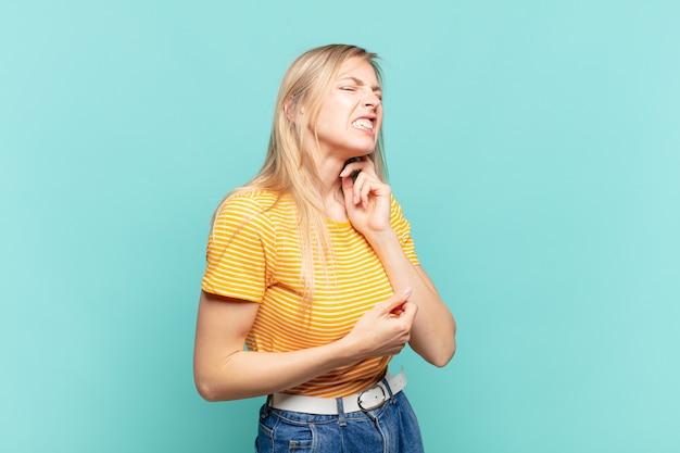 Junge blonde hübsche frau, die sich gestresst, frustriert und müde fühlt, sich den schmerzhaften nacken reibt, mit einem besorgten, unruhigen blick