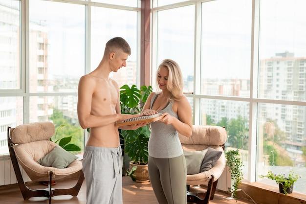 Junge blonde hübsche sportlerin, die yoga-massagepad berührt, das von ihrem ehemann oder fitnesstrainer gehalten wird, der ihr über seine wirksamkeit erzählt