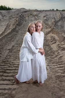 Junge blonde hübsche zwillinge, die am sandsteinbruch im eleganten weißen kleid aufwerfen