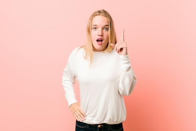 Junge blonde jugendlichfrau, die eine idee, inspirationskonzept hat.