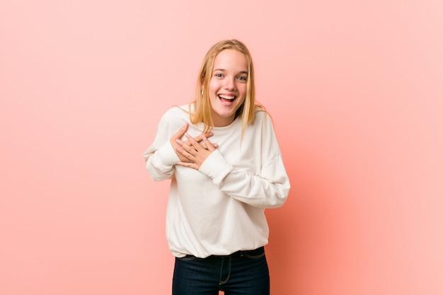 Junge blonde jugendlichfrau, die hände auf herzen, konzept des glückes halten lacht.