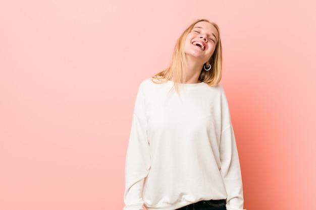 Junge blonde jugendlichfrau entspannte sich und glückliches lachen, der ausgedehnte hals, der zähne zeigt.