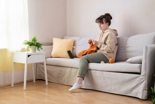 Junge blonde kaukasische frau, die allein auf sofa zu hause strickt. pastellneutrale farben.