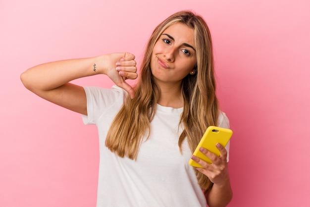 Junge blonde kaukasische frau, die ein gelbes handy lokalisiert zeigt, das eine abneigungsgeste zeigt, daumen nach unten