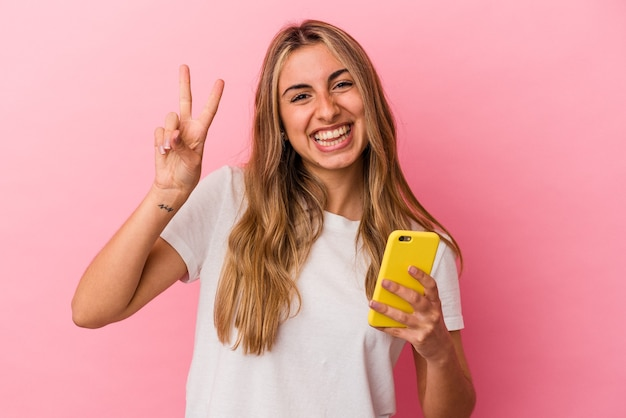 Junge blonde kaukasische frau, die ein gelbes handy lokalisiert zeigt nummer zwei mit den fingern hält