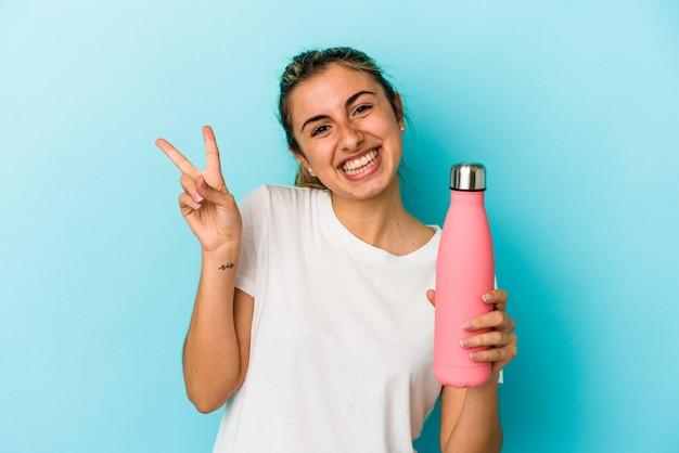 Junge blonde kaukasische frau, die ein thermo lokalisiert auf blauer wand freudig und sorglos hält, das ein friedenssymbol mit den fingern zeigt