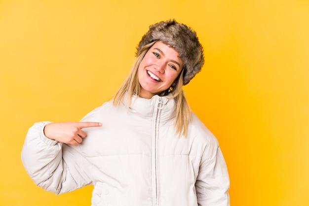 Junge blonde kaukasische frau, die eine isolierte person der winterkleidung trägt, die von hand auf einen hemdkopierraum zeigt, stolz und zuversichtlich