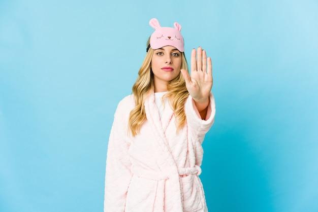 Junge blonde kaukasische frau, die einen pyjama trägt, der mit ausgestreckter hand steht und stoppschild zeigt, das sie verhindert.