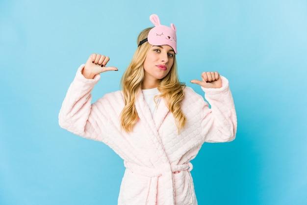 Junge blonde kaukasische frau, die einen pyjama trägt, fühlt sich stolz und selbstbewusst, beispiel zu folgen.