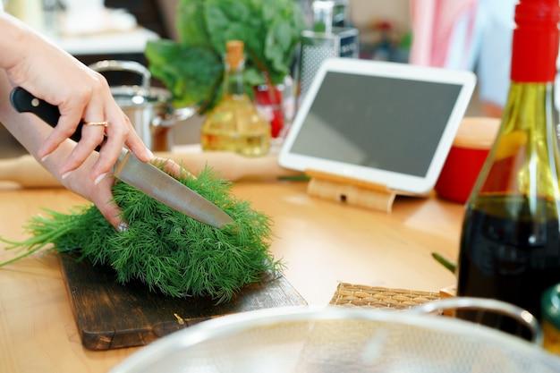 Junge blonde kaukasische frau, die gemüse für salat an ihrer küche schneidet