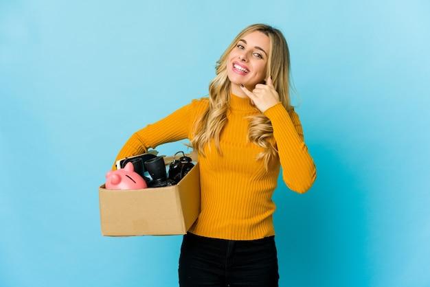 Junge blonde kaukasische frau, die kisten hält, um sich zu bewegen, zeigt eine handy-anrufgeste mit fingern.