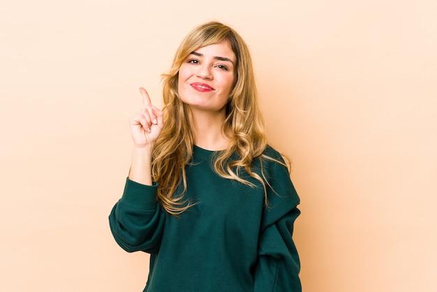 Junge blonde kaukasische frau, die nummer eins mit finger zeigt.