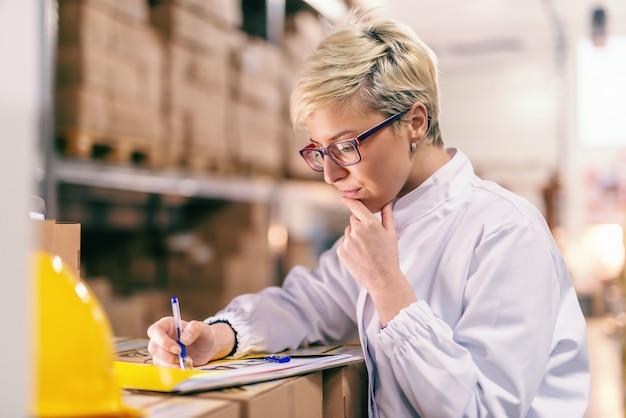 Junge blonde kaukasische frau in der weißen uniform und mit brillen, die papierkram ausfüllen, während im lager stehen.