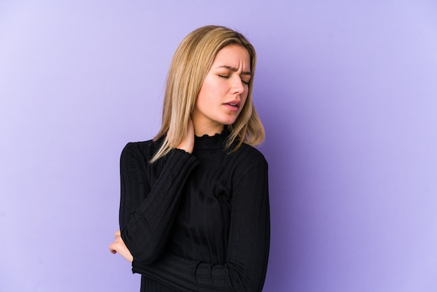 Junge blonde kaukasische frau isoliert, die nackenschmerzen aufgrund von stress, massage und berühren mit der hand hat.