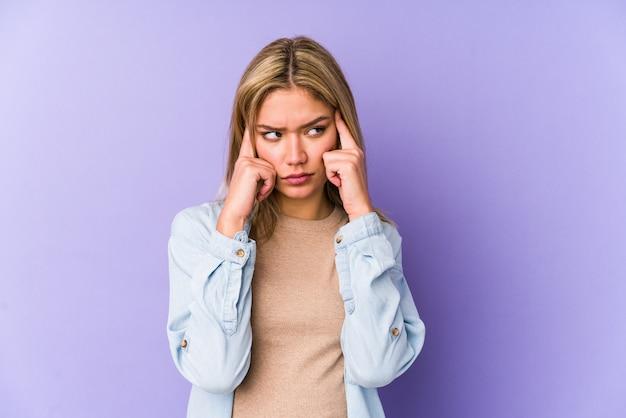 Junge blonde kaukasische frau isoliert konzentriert auf eine aufgabe, zeigefinger zeigen kopf.