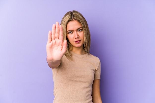 Junge blonde kaukasische frau isoliert stehend mit ausgestreckter hand, die stoppschild zeigt, das sie verhindert.