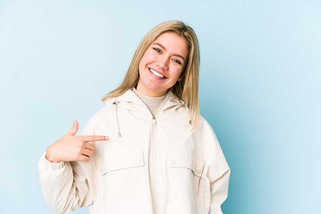 Junge blonde kaukasische frau isolierte person, die von hand auf einen hemdkopierraum zeigt, stolz und zuversichtlich