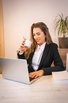 Junge blonde kaukasische frau mit einem kaffee, der mit dem computer arbeitet