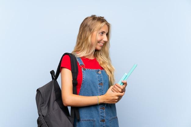 Junge blonde kursteilnehmerfrau über der getrennten blauen wand, die zur seite schaut