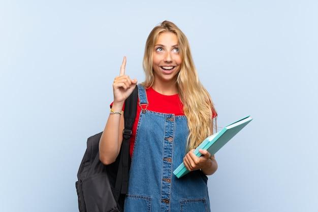 Junge blonde kursteilnehmerfrau über getrennter blauer wand zeigend mit dem zeigefinger eine großartige idee