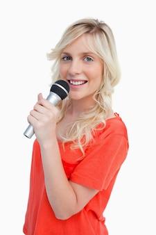 Junge blonde lächelnde frau beim gesang in ein mikrofon