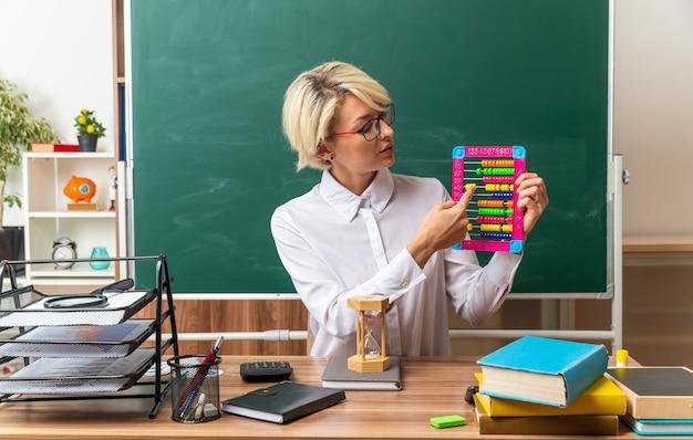 Junge blonde lehrerin mit brille, die am schreibtisch mit schulmaterial im klassenzimmer sitzt und abakus zeigt, der mit dem finger darauf zeigt