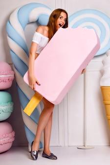 Junge blonde lustige frau, die im studio nahe der riesigen süße aufwirft und großes eis, makronen, süßwarenladen, stilvolle sommerkleidung hält